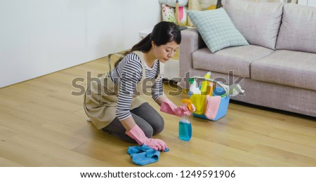 asian girl wearing apron kneeling down on the wooden floor sweeping. young housewife holding cloth and spray cleaning up the room. lady doing housework at home lifestyle concept. #1249591906