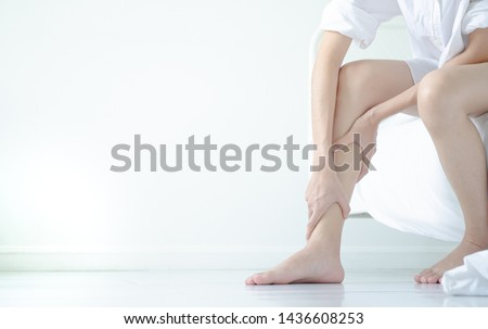 Photo of  Asian girl wearing white dress have leg pain. The woman was squeezing her leg in a white bedroom with sunshine.Warm tone.Do not focus on objects.