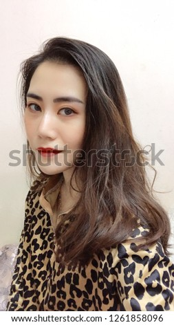 Asian girl wears leopard shirt with white background. #1261858096