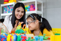 Asian girl with Down's syndrome play toy with her teacher in classroom. Concept disabled kid learning.
