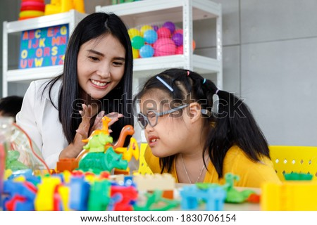 Asian girl with Down's syndrome play toy with her teacher in classroom. Concept disabled kid learning. Stock photo ©