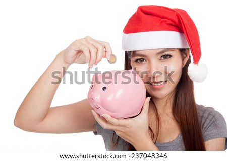 Asian girl with red santa hat put a coin to pink piggy bank  isolated on white background