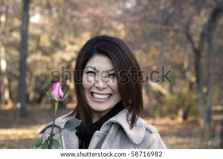 Asian girl with roses outdoors on a fall day.  She is of Japanese ethnicity and was 23 at the time of shoot.