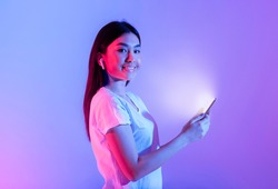 Asian girl with wireless headphones and luminous smartphone in neon