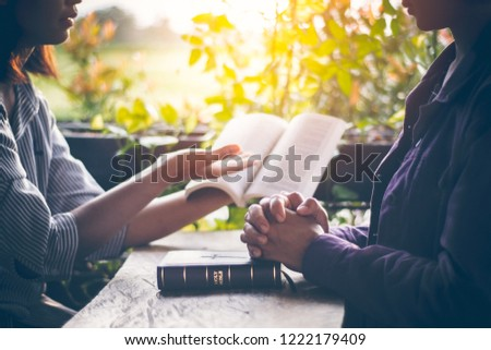 Asian girls are reading the sacred scriptures by pointing to the text of the book. And share the gospel and to explain the meaning of the Bible to her friend understand. Amid the meadows and greenery. #1222179409