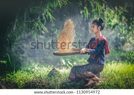 Asian girls cleaning rice in the field.