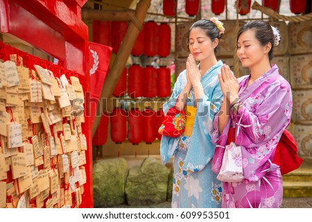 Asian girls wearing japan traditional kimono making a wish near Ema, Ema are small wooden plaques used for wishes by shinto believe. Girlfriends pray close eyes, red lantern background. #609953501