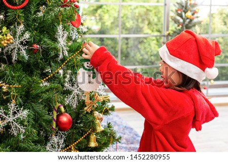 Asian girls wearing red dresses are decorating Christmas trees. Children opening presents on Xmas eve. Merry Christmas and Happy new year. #1452280955
