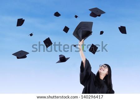 Asian graduate throw graduation cap under blue sky