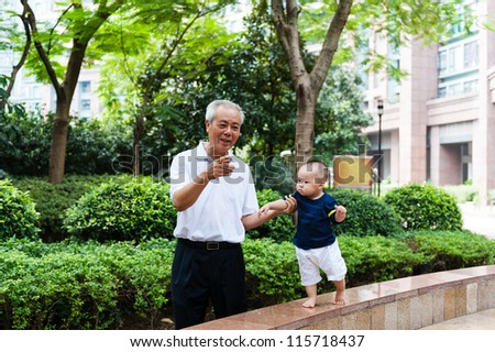Asian grandfather teaching grandson to walk in the garden - stock photo
