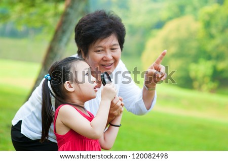 Asian grandmother and granddaughter exploring nature by magnifier