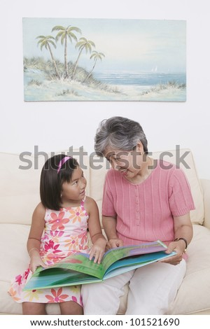 Asian grandmother and granddaughter reading book