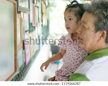 Asian grandmother carrying her granddaughter and enjoy looking at photos of other family members at home - grandparent-grandchild relationship building