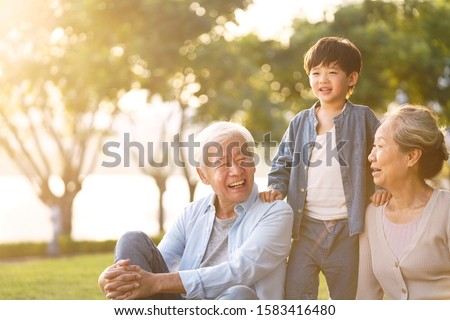 asian grandson, grandfather and grandmother sitting chatting on grass outdoors in park at dusk