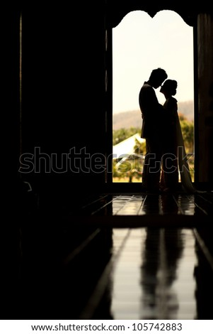 Asian groom and bride embrace in front of boutique door