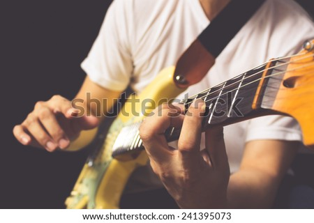 asian guitarist / musician plays electric guitar, isolated on black & old color film processed