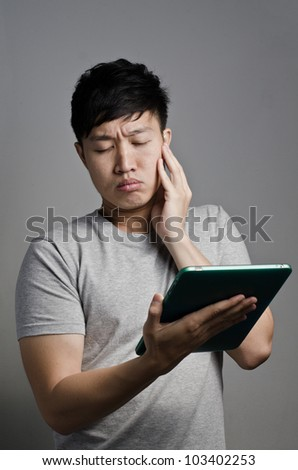Asian guy find something exciting or scary on his tablet