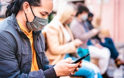 Asian guy using smart phone covered by face mask on Covid second wave - New normal lifestyle concept with milenial people watching news on mobile smartphone - Shallow depth of field with focus on eye