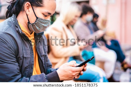 Asian guy using smart phone covered by face mask on Covid second wave - New normal lifestyle concept with milenial people watching news on mobile smartphone - Shallow depth of field with focus on eye Stock photo ©
