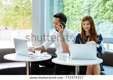 Asian handsome business man use mobile phone for talking him customer and his beautiful colleague working with laptop in modern office or working space. Project and Business concept.