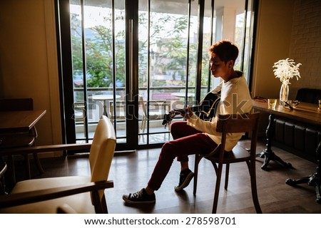 asian handsome guitarist artist man play acoustic guitar in cafe. Shot through the window