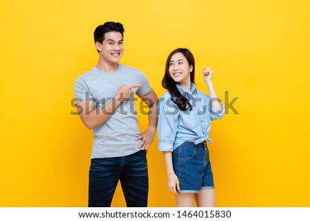 Asian handsome man pointing finger at smiling woman in denim shorts standing together against yellow background in studio