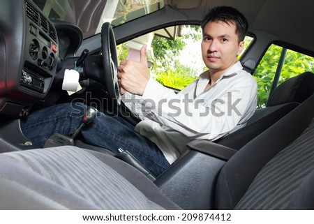 Asian Handsome Man show Thumb-up and Smile in the Car