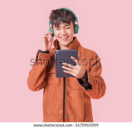 Asian handsome man smiling and listening music by big green headphones by smartphone search. Happy boy from listen to music using wireless technology in to smartphone isolated on pink background.