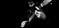 asian handsome musician playing acoustic guitar, bw filter. isolated on black