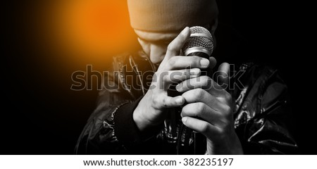 asian handsome singer posing on dynamic microphone. focus on hand, isolated on black