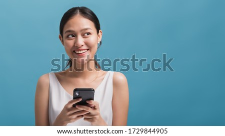 Asian happy beautiful women blogger smiling and holding smartphone isolated in blue colour background with copy space.Concept of online  technology marketing. Photo stock ©