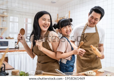 Asian happy family stay at home in kitchen spend time together baking bakery and foods. little kid with parents, father and mother dancing and laughing, enjoy parenting activity relationship in house.