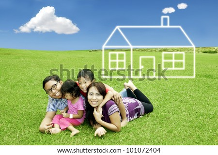 Asian happy family with dream house. Shot in meadow
