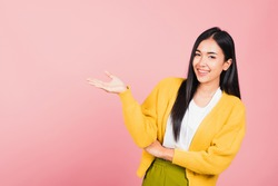 Asian happy portrait beautiful cute young woman smile standing presenting product holding something on palm away side, studio shot isolated on pink background with copy space, female show hand gesture