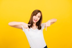Asian happy portrait beautiful cute young woman teen standing wear t-shirt makes gesture two fingers point below down looking to camera isolated, studio shot on yellow background with copy space