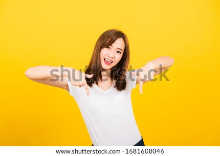 Asian happy portrait beautiful cute young woman teen standing wear t-shirt makes gesture two fingers point below down looking to camera isolated, studio shot on yellow background with copy space Stock photo ©