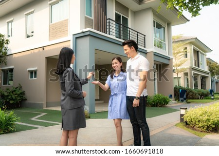 Asian happy smile young couple take keys new big house from real estate agent or realtor in front of their house after signing contract agreement, concept for real estate. Foto stock ©