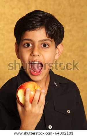 Asian healthy boy eating a red apple