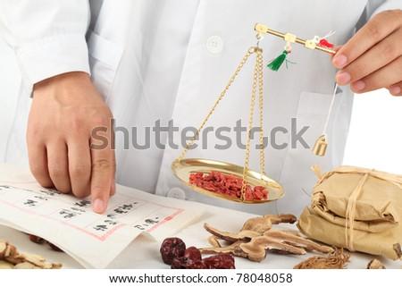 Asian herbalist weighing Chinese medicinal herbs ..