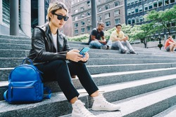 Asian hipster girl in trendy sunglasses jacket using mobile device for reading travel publication in social media, millennial tourist connecting to 4g internet for browsing web text via smartphone