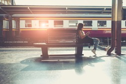 Asian hipster lady photographer sitting at subway station waiting for train. Traveler backpacker girl. Young Woman at platform train railway traveling.  Asian lady hipster photographer sit at subway.