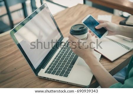 Asian hipster male using smartphone for social network and drinking coffee while working with laptop computer in coffee shop. Freelancer lifestyle and online activity with vintage filter effect