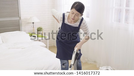 asian housewife woman tired while vacuum cleaning house. wife in apron using cleaner machine on wooden floor feeling back painful. illness frowning housekeeper overworked waist hurting backache. #1416017372