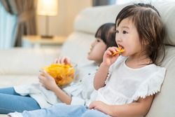 Asian Hungry little girl sibling sisters Puts snack in mouth with hand. Two sweet preschool kid resting on sofa at home enjoy eat fast food, potato chips. Tasty and unhealthy food for children concept