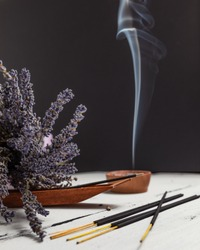 Asian incense sticks and a bouquet of dried lavender on a white wooden table against a dark wall, a wave of incense. Peaceful atmosphere.