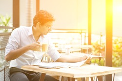 Asian Indian business man reading newspaper while drinking a cup hot milk tea at cafeteria, with beautiful golden sunlight.