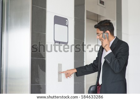 Asian Indian businessman pressing on elevator button, waiting door open to enter inside the lift.