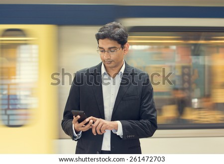 Asian Indian businessman texting using smartphone while waiting train at railway station #261472703