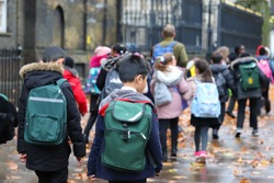 asian, Indian, Chinese &  Caucasian primary student or kids carrying  school bag on their way to visit British museum, City of Westminster, London in rain winter day, with maple leaves on ground