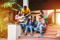 Asian Indian college students playing music with guitar while sitting in campus on stairs or over lawn